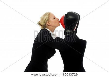 portrait of a young caucasian businesswoman with aggressive air wearing boxing gloves and kissing a