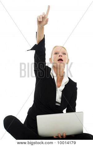 portrait of a young caucasian businesswoman sitting on the floor with arm up and laptop