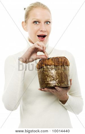 portrait of a young caucasian woman wearing a white turtleneck sweater and holding a panettone