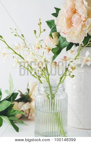 Close Up Of White Orchid Flowers In A Glass Vase With Roses In Background
