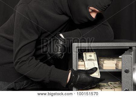 Thief burglar stealing money during home safe codebreaking