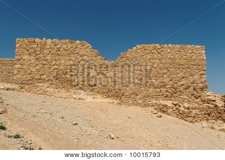 Jagged wall of ancient fortress ruin in the desert