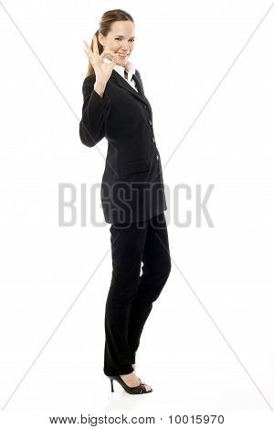 young businesswoman with her hand indicating ok on white background studio