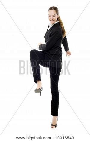 young businesswoman kicking on white background studio