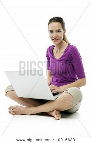 Young woman sitting on the floor with laptop on white background studio