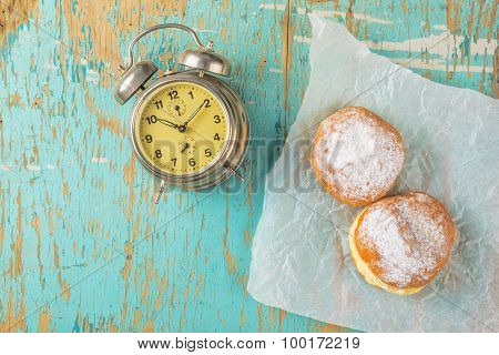 Sweet Sugary Donuts And Vintage Clock On Rustic Table