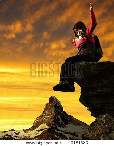 Girl sitting on a rock, in the background Matterhorn at sunset - Pennine Alps, Switzerland.