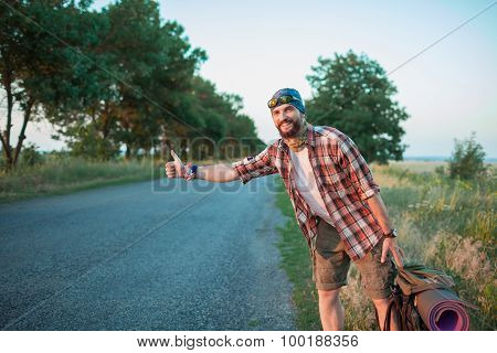 Young smilimg caucasian tourist hitchhiking along a road.