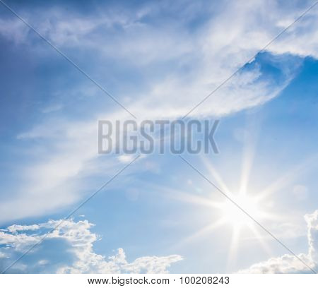 Natural Lens Flare And Radiating Rays In A Blue Sky With Clouds