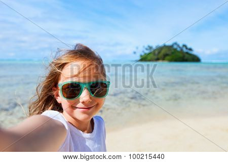 Adorable little girl making selfie in at tropical beach on Rarotonga island during summer vacation