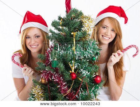 beautiful teen sisters by christmas tree