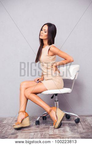Portrait of elegant woman sitting on office chair with backpain on gray background