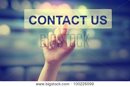 Hand Pressing A Contact Us Button On Blury City Lights Background