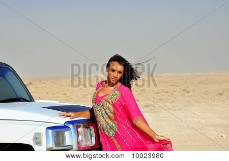 Beautiful Sexy Lady In Pink Oriental Dress Next To Car In Arabic Desert