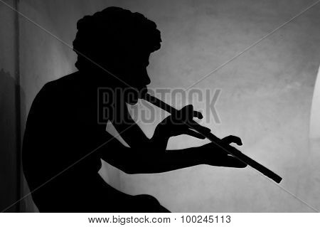A Silhouette Of A Boy Or God Pan Playing A Flute