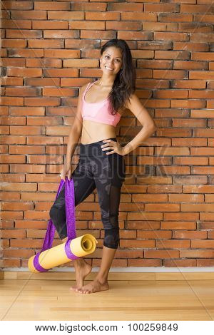 Full body shot of a latin woman in a yoga studio, against a brick wall, with a yoga mat.