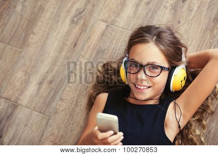 9 years old child is lying down on the floor and listening to music, top view point