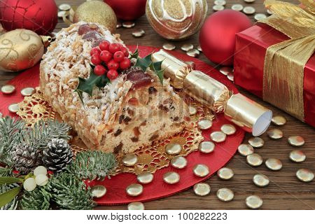 Stollen christmas cake with red and gold decorations, holly, mistletoe and winter greenery. poster