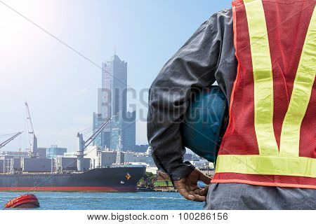 Engineer holding a blue helmet for the safety of workers on the background stock port with cranes an