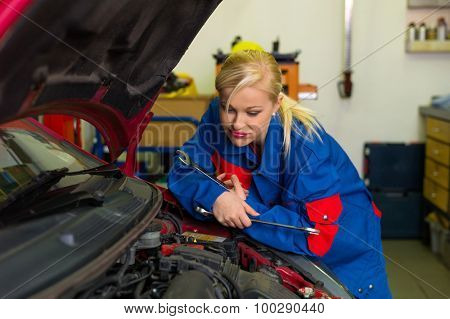a young woman as a mechanic in an auto repair shop. rare occupations for women. car will be repaired in workshop