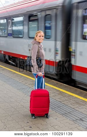a young woman waiting for a train at a station. train holidays