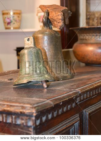 Old Brazen Bells Over Wooden Table