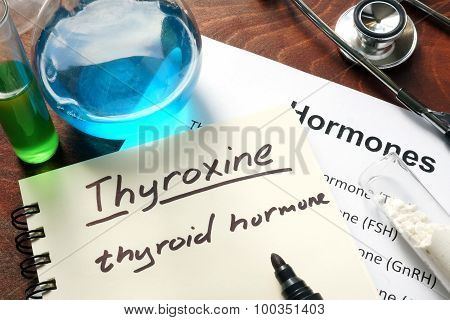 Hormone thyroxine written on notebook.