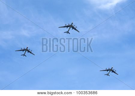 Three Russian military turboprop strategic bombers-missile Tu-95 Bear in flight against the blue sky