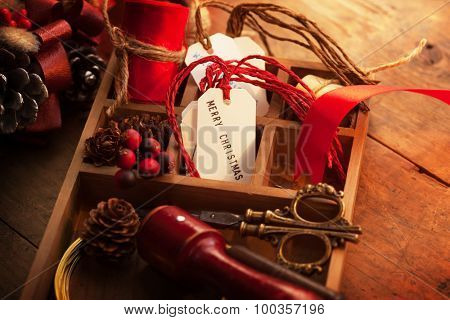 Christmas preparation tray with ribbons and Christmas tags, on an old wooden table with vintage feel.
