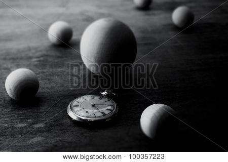 Space and time representation.  Wooden spheres on a grungy old desk, with an pocket watch. Focus on watch. Shallow depth of field.