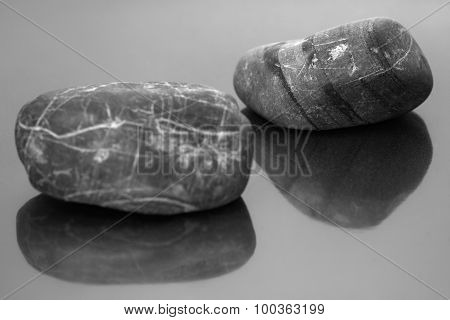 Striped pebbles on a dark glossy background