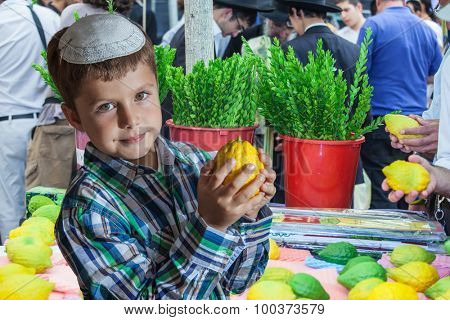 The Jewish holiday of Sukkot,  Holiday market in Jerusalem. Seven year old boy in white skullcap with etrog. Ritual plants - myrtle prepared for sale