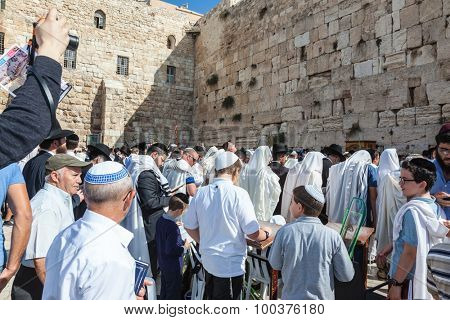 JERUSALEM, ISRAEL - OCTOBER 12, 2014:  Morning autumn Sukkot. The area in front of Western Wall of  Temple filled with people. Crowd of Jewish worshipers in white wearing prayer shawls