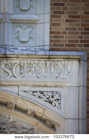 The word School carved into the stone facade of an old schoolhouse.