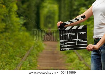 Girl Holding Clapper Board In Her Hands. Tunnel Of Love In Ukraine