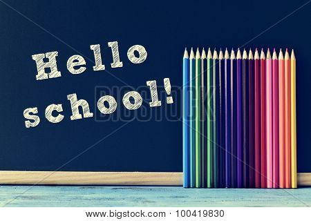the ext hello school written on a chalkboard and a pile of pencil crayons of different colors, on a blue rustic wooden surface