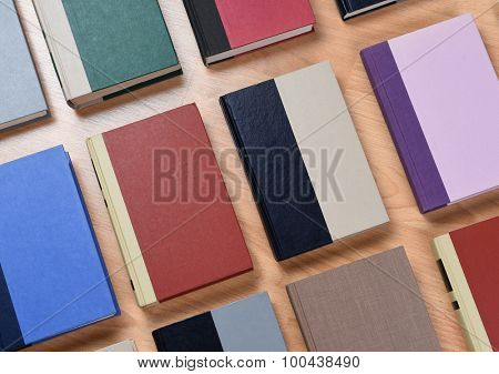 High angle view of rows of assorted text books laid out on a wood student desk. Closeup with the books at an angle.