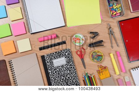 High angle shot of school supplies laid out on a wood desk. Back to School concept with paper, pads, pencils, notebooks, scissors, erasers and more. Horizontal format at an angle.