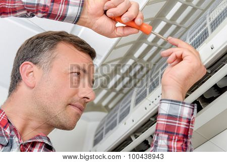 Electrician fitting an air conditioning unit