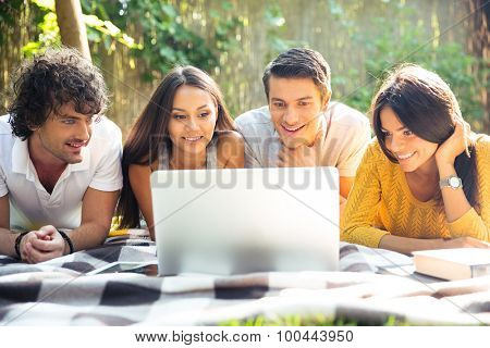 Smiling friends using laptop outdoors