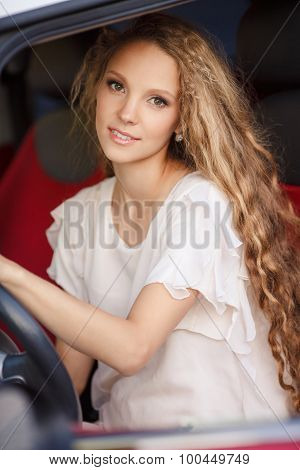 Pregnant brunette girl is sitting in driving seat of the car