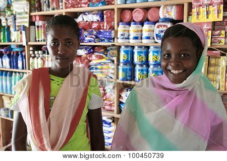 Two Young African Girl Salesgirl In A Shop Household Chemicals.