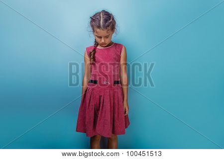 Girl European appearance decade  angry frowns on blue  backgroun