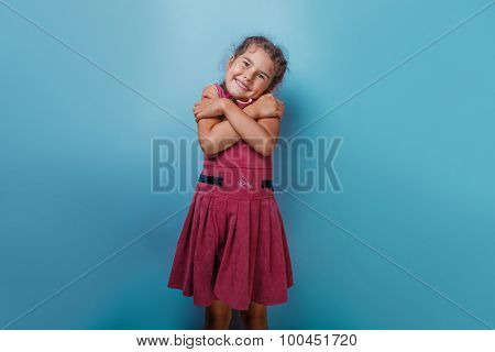 Girl European appearance decade hugging  herself on a blue  back