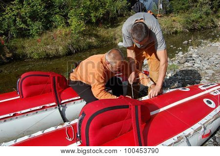 Two men assemble an inflatable catamaran.