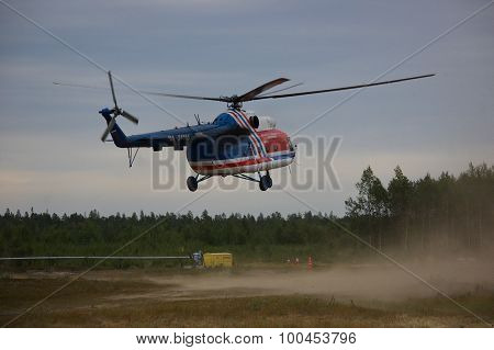 Helicopter Mi-8 landing in cloud of dust on rural airfield.