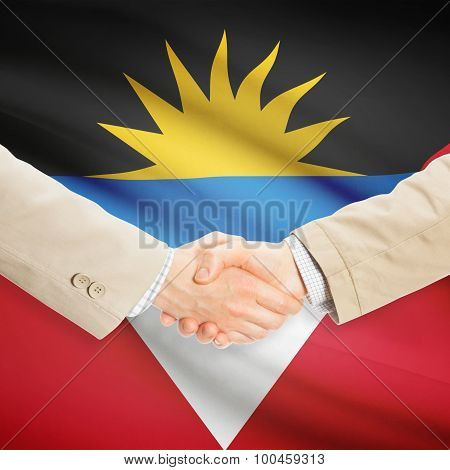 Businessmen shaking hands with flag on background - Antigua and Barbuda poster