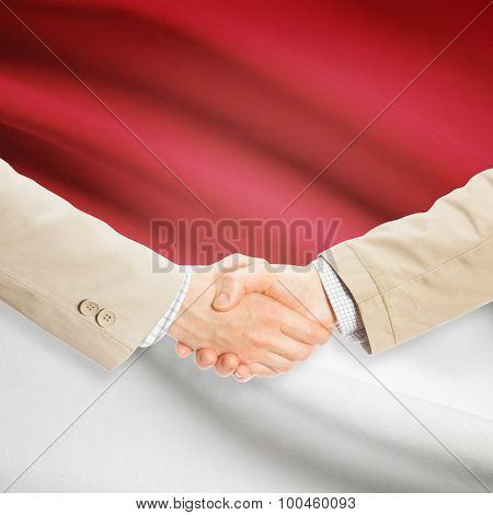 Businessmen shaking hands with flag on background - Monaco poster