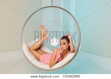 Sexy Girl Lying And Rests In A Transparent Glass Chair