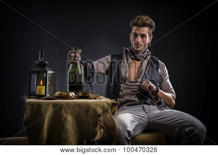 Good Looking Young Man in Pirate Fashion Outfit Sitting next to Table